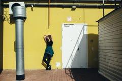 Κορίτσι Brunette στο μαύρο ύφος βράχου, που στέκεται ενάντια στον κίτρινο τοίχο υπαίθρια στην οδό πόλεων Στοκ φωτογραφία με δικαίωμα ελεύθερης χρήσης