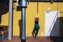 Κορίτσι Brunette στο μαύρο ύφος βράχου, που στέκεται ενάντια στον κίτρινο τοίχο υπαίθρια στην οδό πόλεων Στοκ φωτογραφίες με δικαίωμα ελεύθερης χρήσης