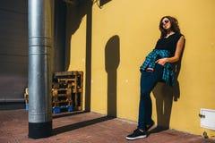 Κορίτσι Brunette στο μαύρο ύφος βράχου, που στέκεται ενάντια στον κίτρινο τοίχο υπαίθρια στην οδό πόλεων Στοκ Φωτογραφίες