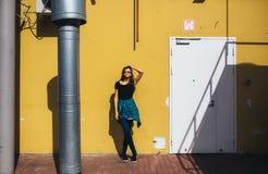 Κορίτσι Brunette στο μαύρο ύφος βράχου, που στέκεται ενάντια στον κίτρινο τοίχο υπαίθρια στην οδό πόλεων Στοκ Εικόνες