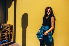 Κορίτσι Brunette στο μαύρο ύφος βράχου, που στέκεται ενάντια στον κίτρινο τοίχο υπαίθρια στην οδό πόλεων Στοκ Φωτογραφία