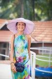 Κορίτσι Brunette στο φόρεμα λουλουδιών και το ρόδινο καπέλο Στοκ Εικόνες
