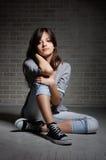 Κορίτσι brunette συνεδρίασης στα παπούτσια γυμναστικής. Στοκ εικόνα με δικαίωμα ελεύθερης χρήσης