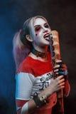Κορίτσι Cosplayer με στο κοστούμι του Harley Quinn αποκριές αποτελούν Στοκ Εικόνες