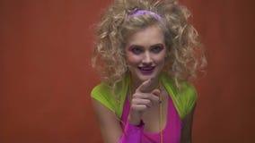κορίτσι disco της δεκαετίας του '80 στα αναδρομικά ενδύματα που δελεάζουν και που χαμογελούν φιλμ μικρού μήκους