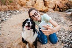 Κορίτσι eyeglasses που παίρνουν selfie με το σκυλί της στο smartphone Στοκ Φωτογραφίες