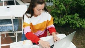 Κορίτσι Freelancer που εργάζεται με το lap-top στον υπαίθριο καφέ απόθεμα βίντεο