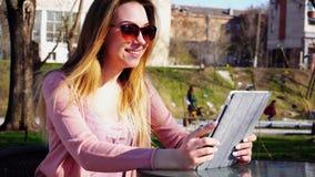 Κορίτσι Gladden που κάνει την τηλεοπτική κλήση από την ταμπλέτα στο φίλο στο πάρκο στοκ φωτογραφία με δικαίωμα ελεύθερης χρήσης