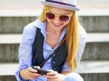 Κορίτσι Hipster που γράφει sms καθμένος στα σκαλοπάτια Στοκ Εικόνες