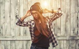 Κορίτσι Hipster στα γυαλιά, τα ακουστικά και το μαύρο beanie στοκ εικόνες
