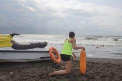Κορίτσι lifeguard στο καθήκον που κρατά έναν σημαντήρα στην παραλία Μηχανικό δίκυκλο νερού, lifeguard πορτοκαλί εργαλείο συντηρητ Στοκ Φωτογραφίες
