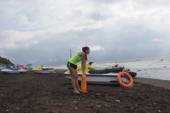 Κορίτσι lifeguard στο καθήκον που κρατά έναν σημαντήρα στην παραλία Μηχανικό δίκυκλο νερού, lifeguard πορτοκαλί εργαλείο συντηρητ Στοκ Εικόνες
