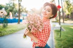 Κορίτσι Pinup με την ανθοδέσμη των λουλουδιών, αναδρομική μόδα Στοκ Φωτογραφία