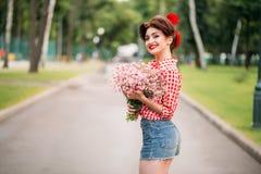 Κορίτσι Pinup με την ανθοδέσμη των λουλουδιών, αναδρομική μόδα Στοκ Φωτογραφίες