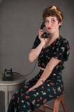 Κορίτσι Pinup στα ανθισμένα προσποιητά χαμόγελα εξαρτήσεων με το τηλέφωνο Στοκ εικόνες με δικαίωμα ελεύθερης χρήσης