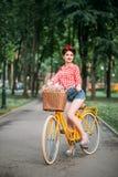 Κορίτσι Pinup στο αναδρομικό ποδήλατο με το backet των λουλουδιών Στοκ Φωτογραφίες
