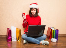 Κορίτσι Santa που αγοράζει on-line για τη συνεδρίαση Χριστουγέννων στο πάτωμα με Στοκ Φωτογραφία