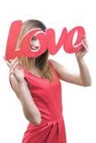 Κορίτσι Smilling, που κρατά την αγάπη τίτλου στα χέρια της Στοκ Εικόνες