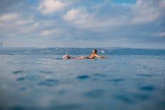Κορίτσι Surfer που κωπηλατεί στην ιστιοσανίδα Γυναίκα με την ιστιοσανίδα στον ωκεανό Surfer και ωκεανός Στοκ φωτογραφία με δικαίωμα ελεύθερης χρήσης