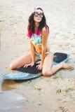 Κορίτσι Surfer στην παραλία στο ηλιοβασίλεμα Στοκ Φωτογραφίες