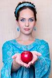 Κορίτσι Unfocused σε ένα μπλε φόρεμα με τη Apple στην παλάμη του χεριού σας Στοκ Φωτογραφίες