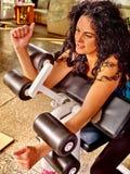Κορίτσι workout στη μηχανή μπουκλών bicep στην αθλητική γυμναστική Στοκ Εικόνα