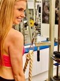 Κορίτσι workout στη μηχανή μπουκλών bicep στην αθλητική γυμναστική Στοκ Εικόνες