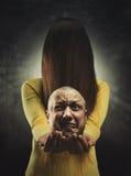 Κορίτσι Zombie με το κεφάλι στα χέρια Στοκ φωτογραφία με δικαίωμα ελεύθερης χρήσης