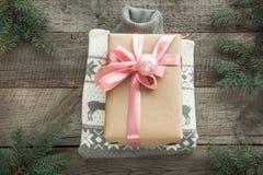 Κορδέλλα δώρων Χριστουγέννων withpink και γκρίζο πουλόβερ στην ξύλινη επιφάνεια Έννοια Χριστουγέννων Στοκ Εικόνες