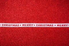 Κορδέλλα Χριστουγέννων στο φωτεινό κόκκινο υπόβαθρο Στοκ Φωτογραφίες