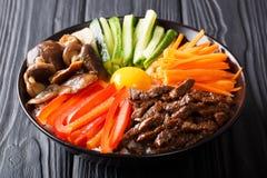 Κορεατικά υγιή τρόφιμα Bibimbap του ρυζιού με το τηγανισμένο βόειο κρέας, ακατέργαστο αυγό, β στοκ φωτογραφία