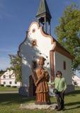 Κορεατική γυναίκα και ξύλινο γλυπτό ST John Nepomuk με το μικρό παρεκκλησι, το χωριό Holasovice, Δημοκρατία της Τσεχίας στοκ εικόνα με δικαίωμα ελεύθερης χρήσης