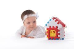 Κοριτσάκι και παιχνίδι, πλαστικό σπίτι που απομονώνεται στο λευκό Στοκ φωτογραφία με δικαίωμα ελεύθερης χρήσης