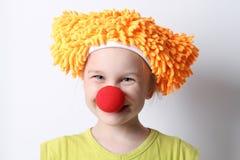 Κοριτσάκι κλόουν με μια κόκκινη μύτη σε μια αστεία ΚΑΠ Στοκ Φωτογραφίες