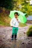 Κοριτσάκι με μια ομπρέλα στα τρεξίματα βροχής μέσω των λακκουβών Στοκ Εικόνες