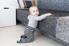 κοριτσάκι 6 μηνών που προσπαθεί να σηκωθεί Στοκ Εικόνες