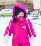 Κοριτσάκι μικρών παιδιών σε ένα ροδανιλίνης παιχνίδι κοστουμιών χιονιού στο χιόνι Στοκ Φωτογραφία