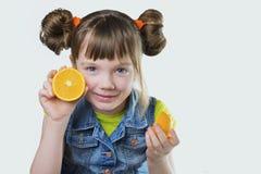Κοριτσάκι που ευλογείται με ένα χαμόγελο και ένα πορτοκάλι στα χέρια Στοκ Φωτογραφίες