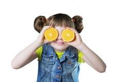 Κοριτσάκι που ευλογείται με ένα χαμόγελο και ένα πορτοκάλι στα χέρια Στοκ Εικόνες