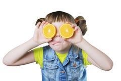 Κοριτσάκι που ευλογείται με ένα χαμόγελο και ένα πορτοκάλι στα χέρια Στοκ φωτογραφία με δικαίωμα ελεύθερης χρήσης