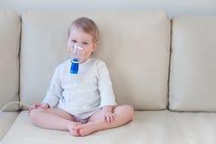 Κοριτσάκι που κάνει την εισπνοή με τη μάσκα στο πρόσωπό της στοκ φωτογραφία