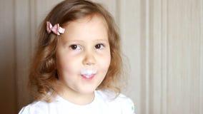 Κοριτσάκι που πίνει ένα ποτό γάλακτος από ένα μπουκάλι, kefir, γαλακτοκομικό προϊόν Παιδί που χαμογελά και που παρουσιάζει άσπρο  φιλμ μικρού μήκους