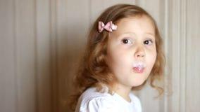 Κοριτσάκι που πίνει ένα ποτό γάλακτος από ένα μπουκάλι, kefir, γαλακτοκομικό προϊόν Παιδί που χαμογελά και που παρουσιάζει άσπρο  απόθεμα βίντεο