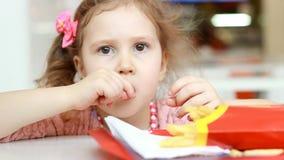 Κοριτσάκι που τρώει τις τηγανιτές πατάτες γρήγορου φαγητού σε έναν καφέ Κινηματογράφηση σε πρώτο πλάνο πορτρέτου φιλμ μικρού μήκους
