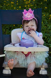 Κοριτσάκι που τρώει το πρώτο κέικ γενεθλίων με το πορφυρό πάγωμα και τη ρόδινη κορώνα στο κεφάλι της Στοκ εικόνες με δικαίωμα ελεύθερης χρήσης