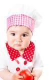 Κοριτσάκι που φορά ένα καπέλο αρχιμαγείρων με την ντομάτα. Στοκ φωτογραφία με δικαίωμα ελεύθερης χρήσης