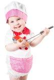 Κοριτσάκι που φορά το καπέλο αρχιμαγείρων με τα λαχανικά και το τηγάνι που απομονώνεται στο άσπρο υπόβαθρο. Η έννοια των υγιών τρο Στοκ Εικόνες