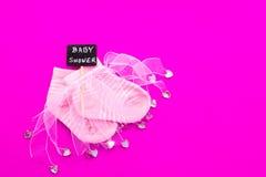 Κοριτσάκι - ρόδινες και άσπρες κάλτσες με την κορδέλλα στο ρόδινο υπόβαθρο με το ντους μωρών στο σημάδι πινάκων Στοκ Φωτογραφίες