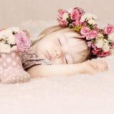 Κοριτσάκι ύπνου στα λουλούδια, όμορφο εκλεκτής ποιότητας υπόβαθρο Στοκ Φωτογραφία