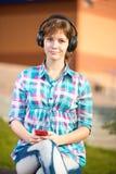 Κοριτσιών κολλεγίων χαμόγελου νέο σε ένα τηλέφωνο κυττάρων Στοκ φωτογραφίες με δικαίωμα ελεύθερης χρήσης